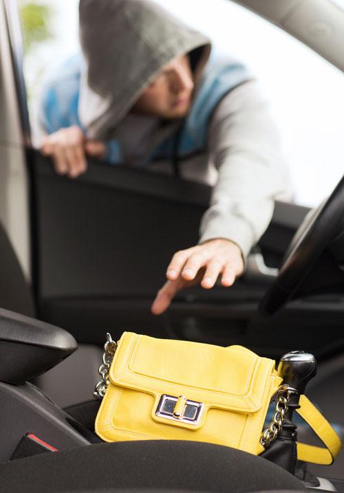 Thief stealing purse from car